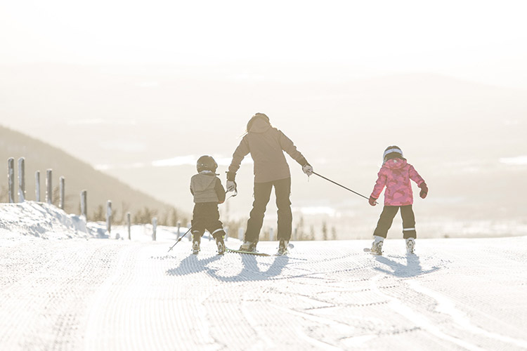 Vuxen kvinna med två mindre barn som lär sig åka slalom.