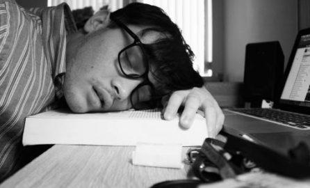 Sömn. Trött ung man sover vid laptop.